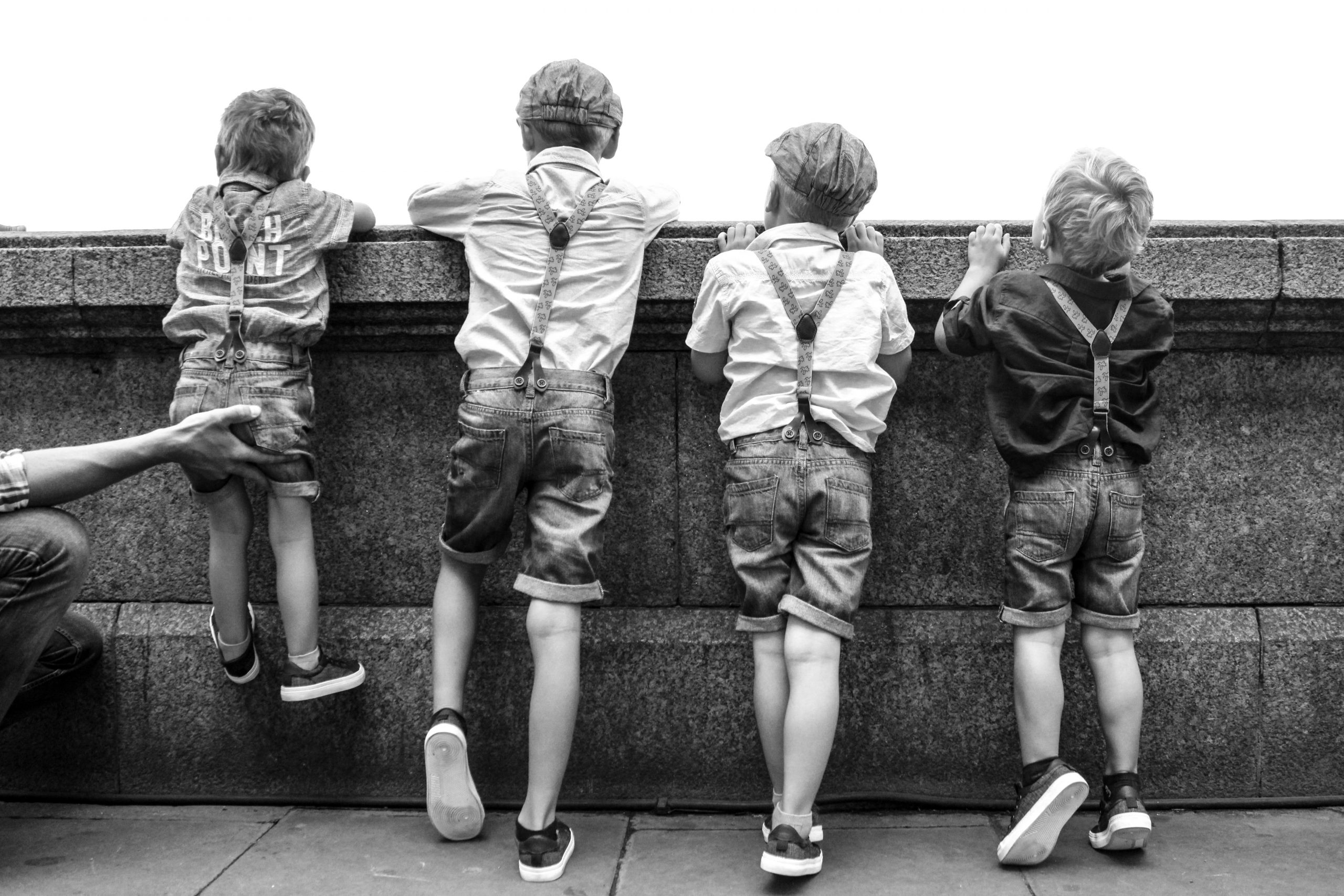 4 Brothers looking over a wall in London