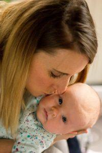 Mum kissing baby girl